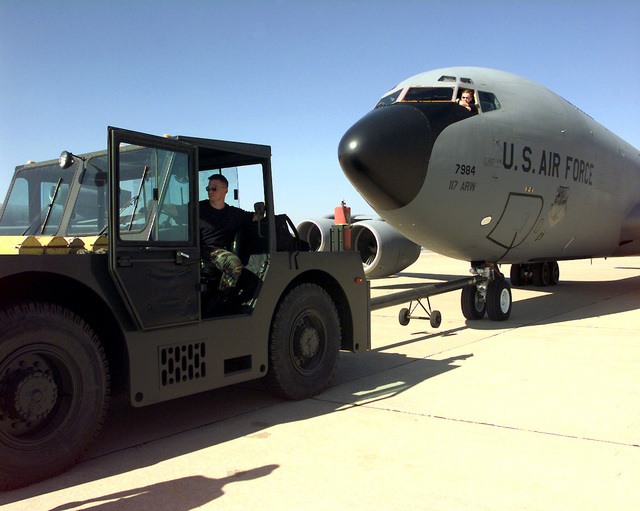 US Air Force STAFF Sergeant Scott Lewis drives the MB2 Tow Tractor as AIRMAN First Class Mike Miller performs the brake operation on a USAF KC-135 Stratotanker, as they move the aircraft to another location. SSGT Lewis and A1C Miller, both Crewcheifs with the 319th Aircraft Generation Squadron (AGS) Grand Forks Air Force Base, North Dakota, depoloyed to Moron Air Base, Spain, in support of Phoneix Duke II