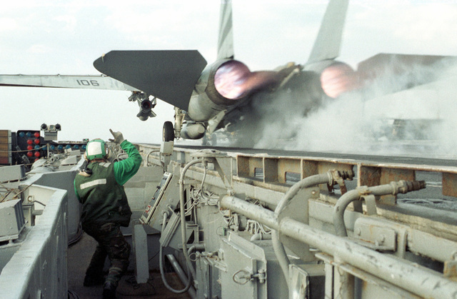 US Navy Aviation Boatswain Mate (Launch and Recovery Equipment Operator) 3rd Class (AB3) Joshua Schwandt signals a clear launch of an F-14 Tomcat from the ships port side catapult. Aboard the conventional aircraft carrier USS INDEPENDENCE (CV 62) which is forward deployed in the Persian Gulf to enforce UN sanctions against Iraq during Operation SOUTHERN WATCH, 22 February 1998
