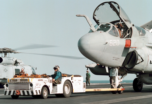 A US Navy flight deck tractor operator repositions an EA-6B Prowler, Tactical Electronic Warfare Squadron One Three Seven (VAQ-137) during daily flight quarters on board the nuclear powered aircraft carrier USS GEORGE WASHINGTON (CVN 73). The GEORGE WASHINGTON and VAQ-137 are currently conducting operations in the Persian Gulf to enforce UN sanctions against Iraq. Operation SOUTHERN WATCH, 25 February 1998