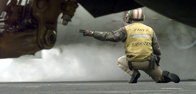 "United States Navy, Lieutenant John Tucker, the ""Indy shooter"", gives the launch signal for an aircraft on the flight deck of the conventional aircraft carrier USS INDEPENDENCE (CV 62) in the Persian Gulf. Operation Southern Watch, 28 February 1998"