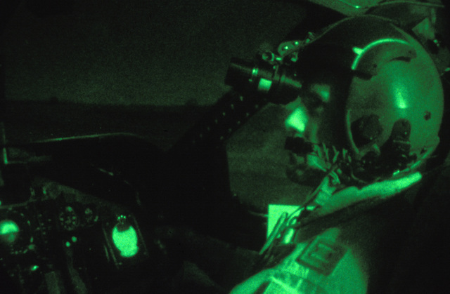 Captain (CPT) John Delapp, a pilot with the 16th Airlift Squadron, gazes through a pair of night-vision goggles while landing his C-141 Starlifter on a blacked out runway, during Special Operations training