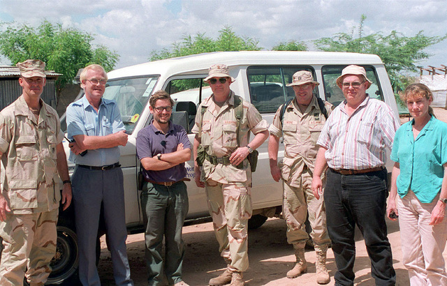 (from left to right) US Marine Corps General Whitlow, Joint Task Force Commander, followed by Stig Larson, World Food Programme, Stevie, World Food Programme, COL O'donovan, Mission Commander, US Army Captain Moore US Army Civil Affairs, Ron Libby, USDA Forest Service, and Deanne Shulman, USDA Forest Service, pose for a group photo at the Garissa Camp during Operation NOBLE RESPONSE '98. (Duplicate image, see also DMSD0106033 or search 980302M4605W004)