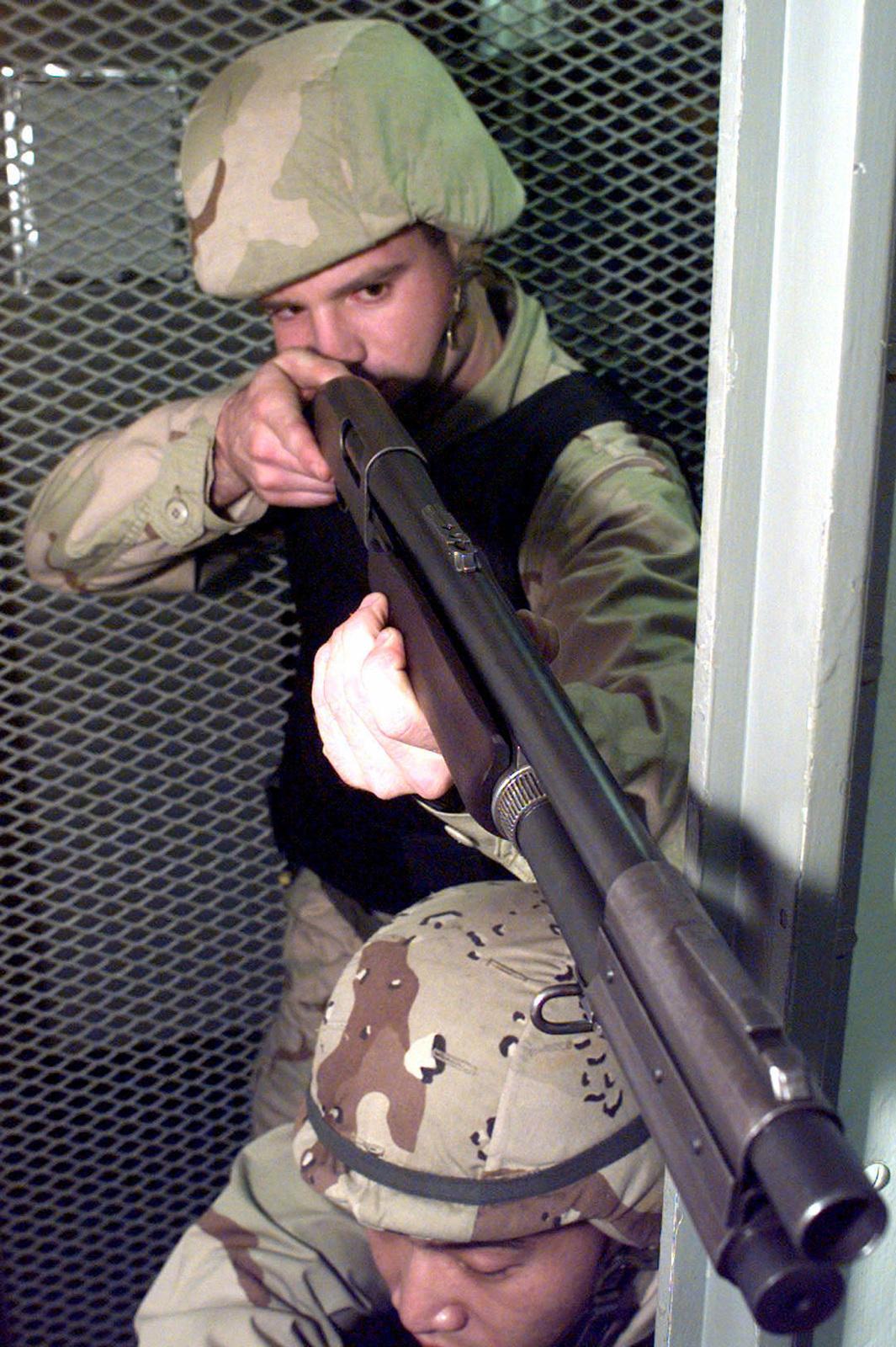 US Marine Corporal David Lampron (Top) readies a 12 gauge shotgun