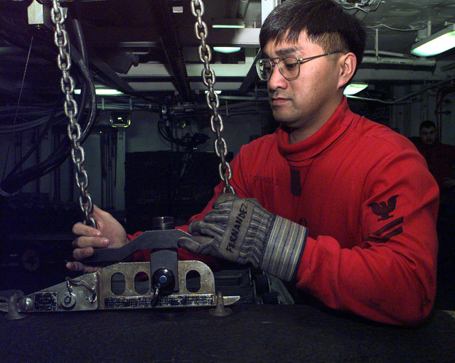 US Navy Weapons Ordnance SPECIALIST, PETTY Officer Fernandez, aboard the Forrestal Class Aircraft Carrier, USS INDEPENDENCE (CV 62), attaches a grappling hook to a 500 pound bomb that is to be lifted up the weapons elevator to the ship's hangar deck. The INDEPENDENCE is in the Persian Gulf participating in the Southwest Asia build-up