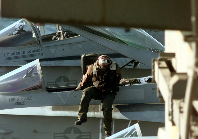 A US Navy Sailor, known as the plane captain, slinks down the side of a F/A-18A Hornet aircraft aboard the Forrestal Class AIrcraft Carrier, USS INDEPENDENCE (CV 62), during flight operations in the Persian Gulf