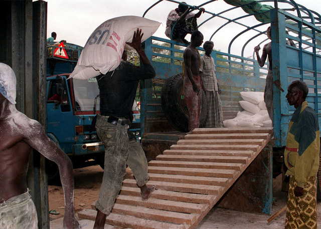 A worker at the World Food Program (WFP) warehouse in Garissa, loads one of the 8 ton trucks used to transport food to Dadob during Joint Task Force Kenya, operation Noble Response. (Duplicate image, see also DM-SD-02-04676 or search 980303-M-4605W-001)