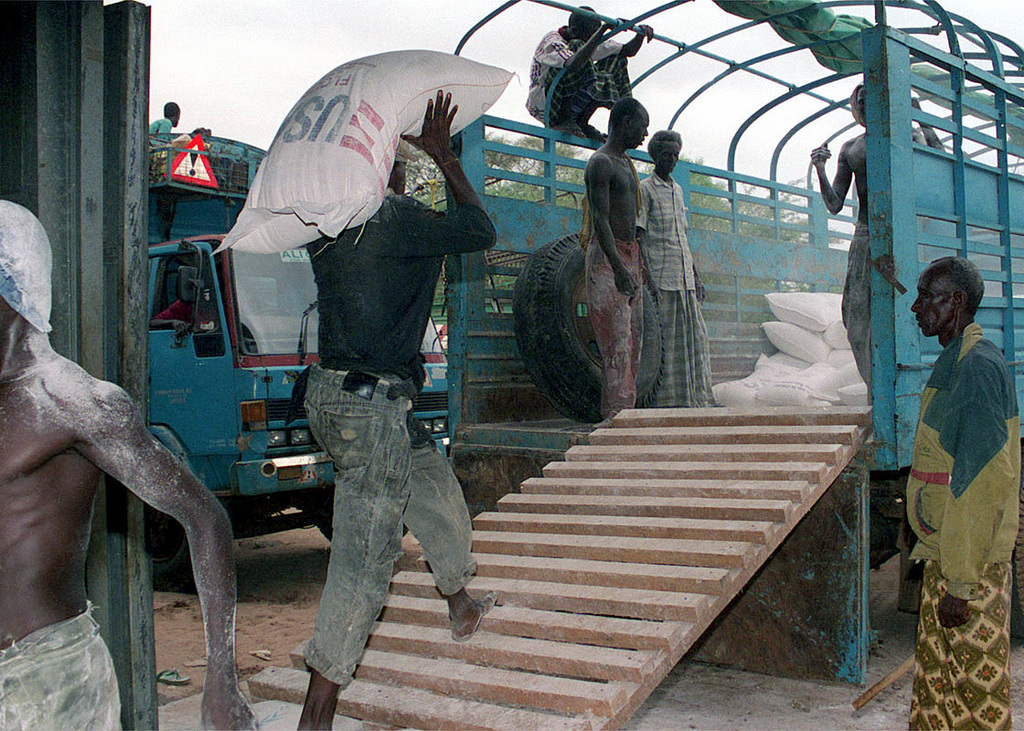 A worker at the World Food Programme (WFP) warehouse in Garissa, loads one of the 8 ton trucks used to transport food to Dadob during Operation NOBLE RESPONSE '98. (Duplicate image, see also DM-SD-01-06040 or search 980303-M-4605W-001)