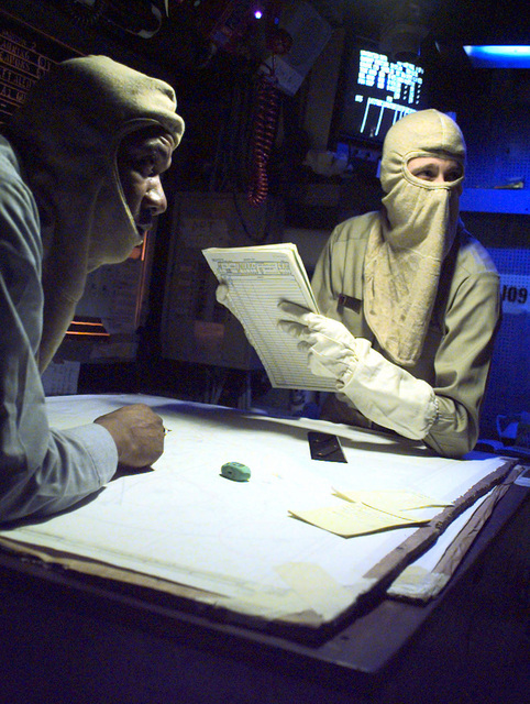 Two US Navy Sailors review charts and plot on a map in the Forrestal Class Aircraft Carrier, USS INDEPENDENCE's (CV 62), Combat Direction Center during a General Quarters drill while the ship is deployed in the Persian Gulf as part of Southwest Asia build-up
