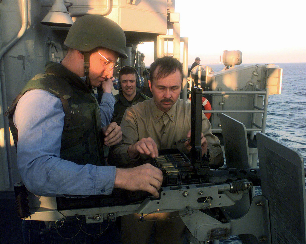 US Navy CHIEF GUNNER's Mate Lonnie Jones (Right) shows Fire Control Technician 3rd Class Carl Mendleson (Left) the proper way to align the ammo (ammunition) belt for a M-2, .50 caliber machine gun, aboard the Oliver Hazard Perry Class Guided Missile Frigate, USS SAMUEL B. ROBERTS (FFG 58). The ROBERTS is patrolling the Persian Gulf in support of the Southwest Asia build-up