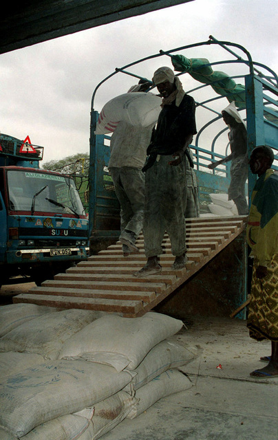 Workers at the World Food Program (WFP) warehouse in Garissa, load corn onto the 8-10 ton truck used to transport food to Dadob in support of Joint Task Force Kenya, operation Noble Response. (Duplicate image, see also DM-SD-02-04681 or search 980303-M-4605W-007)