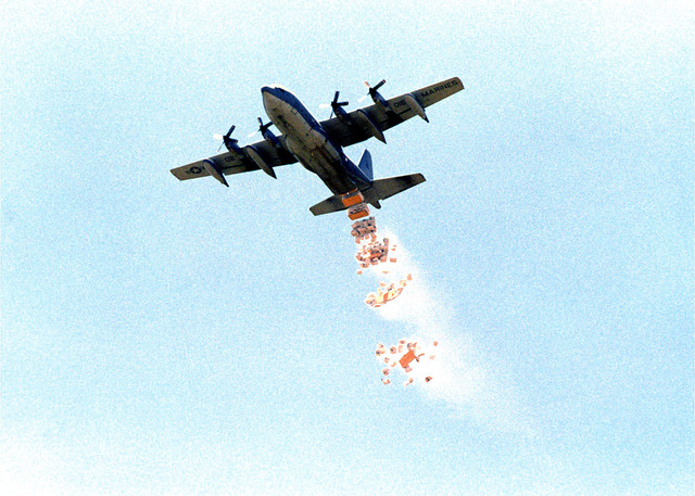 "A United States Marine Corps C-130 Hercules aircraft, from Marine Aerial Refueling Transport Squadron 352 (VMGR 352) Piloted by Major Falcom ""Bumper"" (not shown), drops a load of World Food Program (WFP) corn on a drop zone outside the village of Madogashi during Joint Task Force Kenya, operation Noble Response. (Duplicate image, see also DMSD0204683 or search 980304M4605W002)"
