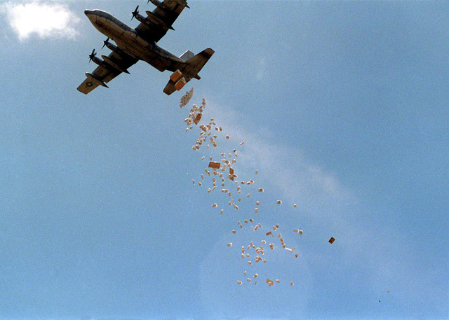 "A United States Marine Corps C-130 Hercules aircraft, from Marine Aerial Refueling Transport Squadron 352 (VMGR 352) Piloted by Major Falcom ""Bumper"" (not shown), drops a load of World Food Program (WFP) corn on a drop zone outside the village of Madogashi during Joint Task Force Kenya, operation Noble Response. (Duplicate image, see also DM-SD-02-04685 or search 980304-M-4605W-004)"