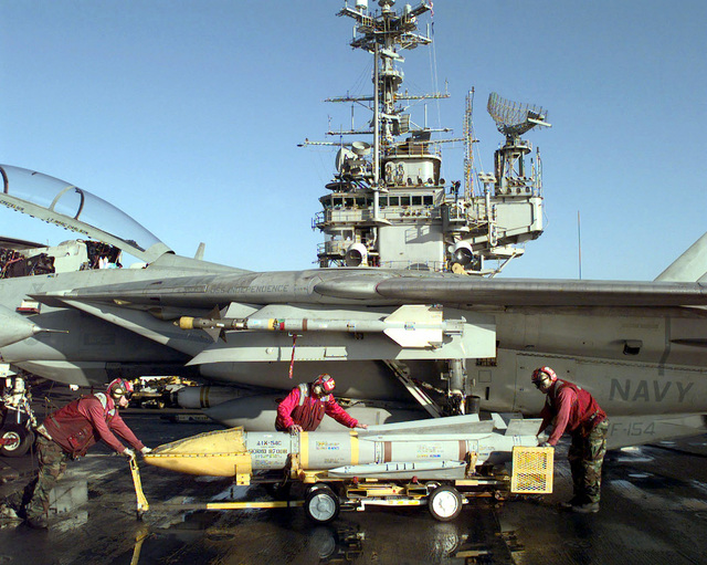 Sailors from Forrestal Class, USS INDEPENDENCE (CV-62) ordnance department load a Pheonix missile on the wings of an F-14 fighter before it departs the carrier in the Arabian Sea for the Southwest Asia (SWA) build-up