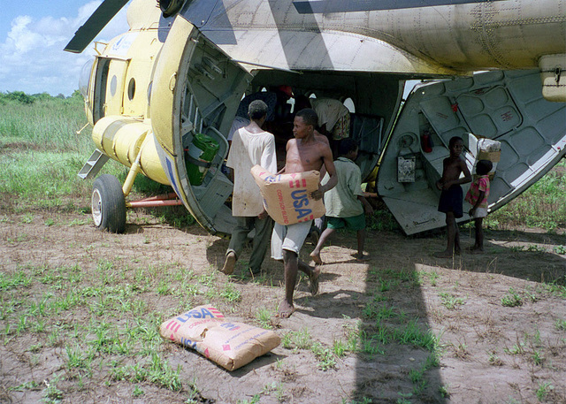 Locals from the Wema Catholic Camp in southern Kenya unload a World Food Programme United Nations MI8 during Operation NOBLE RESPONSE '98, Joint Task Force Kenya