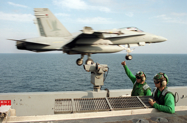 An F/A-18 Hornet launches past sailors on the flight deck of USS GEORGE WASHINGTON (CVN-73) while underway in the Arabian Sea. The ship is in to the area as part of the Southwest Asia (SWA) build-up of forces in reaction to Iraq's refusal of U.N. sponsored weapon's inspections
