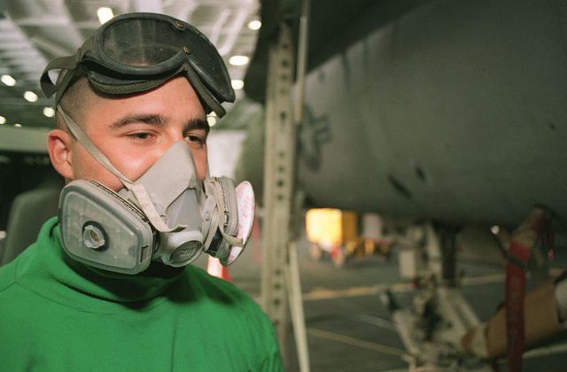 LCPL Chris Benavides dons a face mask while spraying primer (not shown) on an F/A-18 Hornet aircraft in the hangar of USS GEORGE WASHINGTON (CVN-73). The ship is in the Arabian Sea as part of the Southwest Asia (SWA) build-up of forces in reaction to Iraq's refusal of U.N. sponsored weapon's inspections