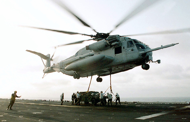 """A Helicopter Support Team from Marine Helicopter Medium Squadron 264 (HMM-264) attach a High-Mobility Multipurpose Wheeled Vehicle (HMMWV) to a CH-53 """"Super Stallion"""" during an equipment transport exercise aboard the Wasp Class Amphibious Assault Ship, USS WASP (LHD 1). The HMMWV was carried to troops (Not shown) waiting ashore"""