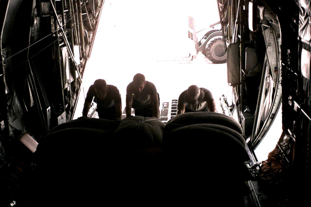 Corporals Dudley, Shelley, and Attikisson, Load Masters for Marine Aerial Refueling Transport Squadron 352 (VMGR 352), load up food onto the the back of a C-130 Hercules aircraft in preparation for an air delivery mission in northern Kenya in support of Joint Task Force Kenya, operation Noble Response