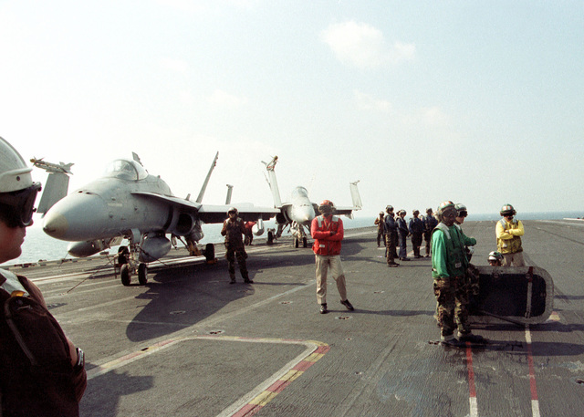 US Navy flight deck personnel await the next launch/recovery cycle aboard the Forrestal Class Aircraft Carrier, USS INDEPENDENCE (CV 62). US Navy F/A-18 Hornets from Strike Figher Squadron 195 (VFA-195) are seen on the deck. The INDEPENDENCE is deployed to the Persian Gulf in support of Operation Southern Watch