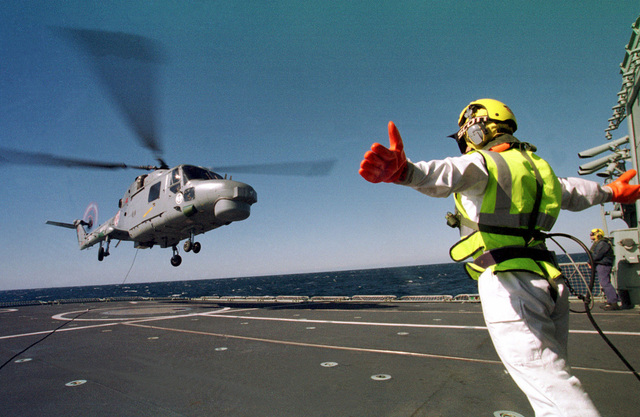 A Portuguese Flight Deck Officer directs a Portuguese Navy Lynx Mk-95 helicopter off the flight deck of the Vasco de Gama Class Frigate, NRP VASCO DE GAMA (F 330), after a simulated force boarding aboard the German Bremen Class Frigatem FGS AUSGBURG (Not shown), March 12th, 1998. The helicopter crew is operating with the VASCO DE GAMA and other NATO Navy ships (Not shown) off the coast of Portugal during exercise Strong Resolve '98, Crisis South