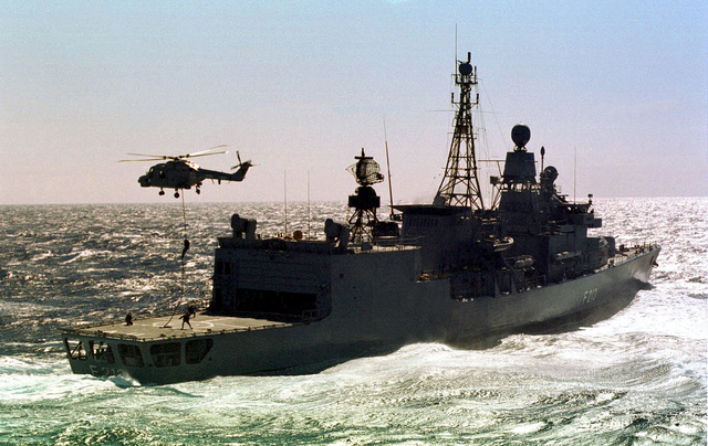 Portuguese Marines fastrope from a Portugese Lynx Mk-95 helicopter to the flight deck of the German, Bremen Class Frigate, FGS AUGSBURG (F 213), during a simulated force boarding on March 12th, 1998. The Marines, from the 1ST Marine Battalion, are operating off the Portugese Vasco de Gama Class Frigate, NRP VASCO DE GAMA (F 330) (Not shown), which is operating with other NATO navy ships (Not shown) off the coast of Portugal during exercise Strong Resolve 98, Crisis South