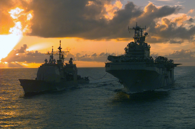 As the sun sets over the Australian coast, USS VINCENNES (CA 44) (left) is fueled up by USS BELLEAU WOOD (LHA 3). The RAS (Refueling At Sea) took place as the ships of the Belleau Wood Amphibious Ready Group, embarked with the 31st Marine Expeditionary Unit (Special Operations Capable), traveled to Shoalwater Bay Training Area, Australia to participate in exercise VALIANT USHER 98-1, a combined exercise with the Australian Defense Force
