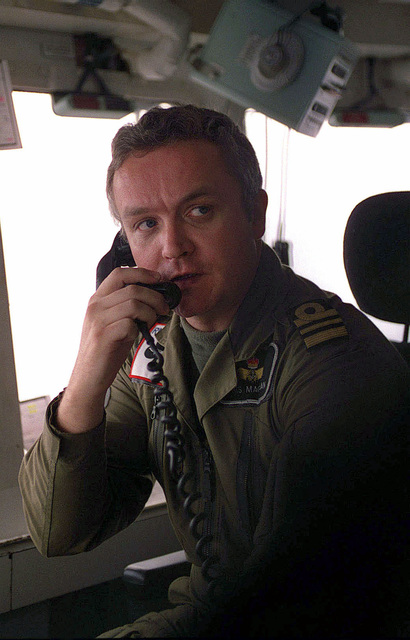 "British Royal Navy Lieutenant Commander Chris MacBean, the Assistant Air Operations Officer of the Invincible Class Aircraft Carrier, HMS ILLUSTRIOUS (RO 6), gives the ""clear deck"" call during flight operations. The British vessel is operating in the Persian Gulf in support of the Southwest Asia build-up"