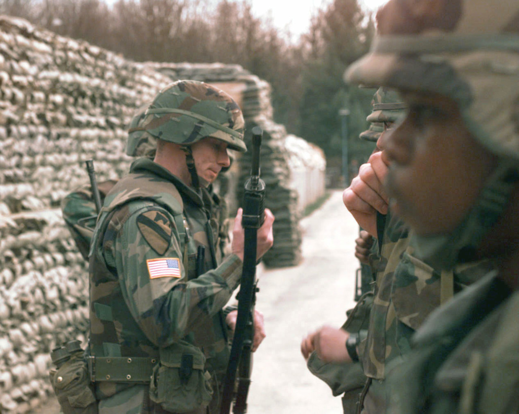 SSG Pousard, in woodland camouflage BDU, helmet, and body armor, of the 1ST Armored Division, Bad Kreuznach, Germany, inspects a guard's weapon at the start of the duty shift during JOINT GUARD