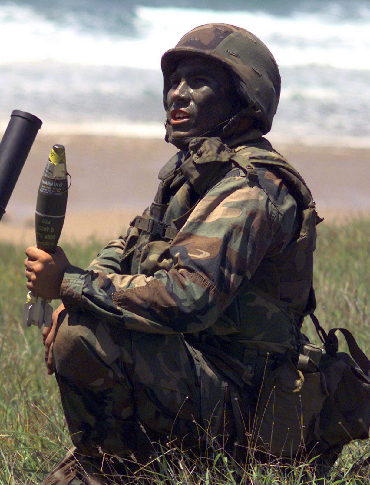 A mortarman stands by to load a round into a 60mm mortar at