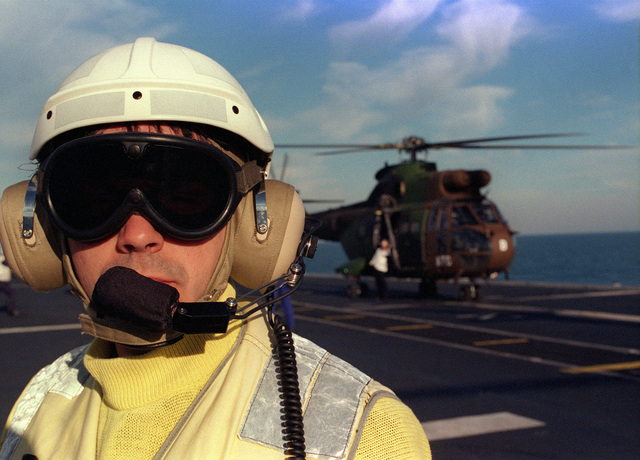A Spanish Navy aircraft director stands by onboard the Spanish Prince de Asturias Class Aircraft Carrier PRINCIPE DE ASTURIA (R 11), while conducting flight operations off the coast of Rota, Spain. The carrier is particapating in exercise Strong Resolve '98. The exercise, NATO's largest combinded exercise since the end of the Cold War, is taking place in Norway, Spain, Portugal and surrounding waters and will run through March 21st, 1998. Twenty-five nations are particapating in the exercise, with ten being Non-NATO nations. Spain and Portugal are hosting the crisis south scenario, which is the peacekeeping portion of the exercise and consist of over 25,000 people
