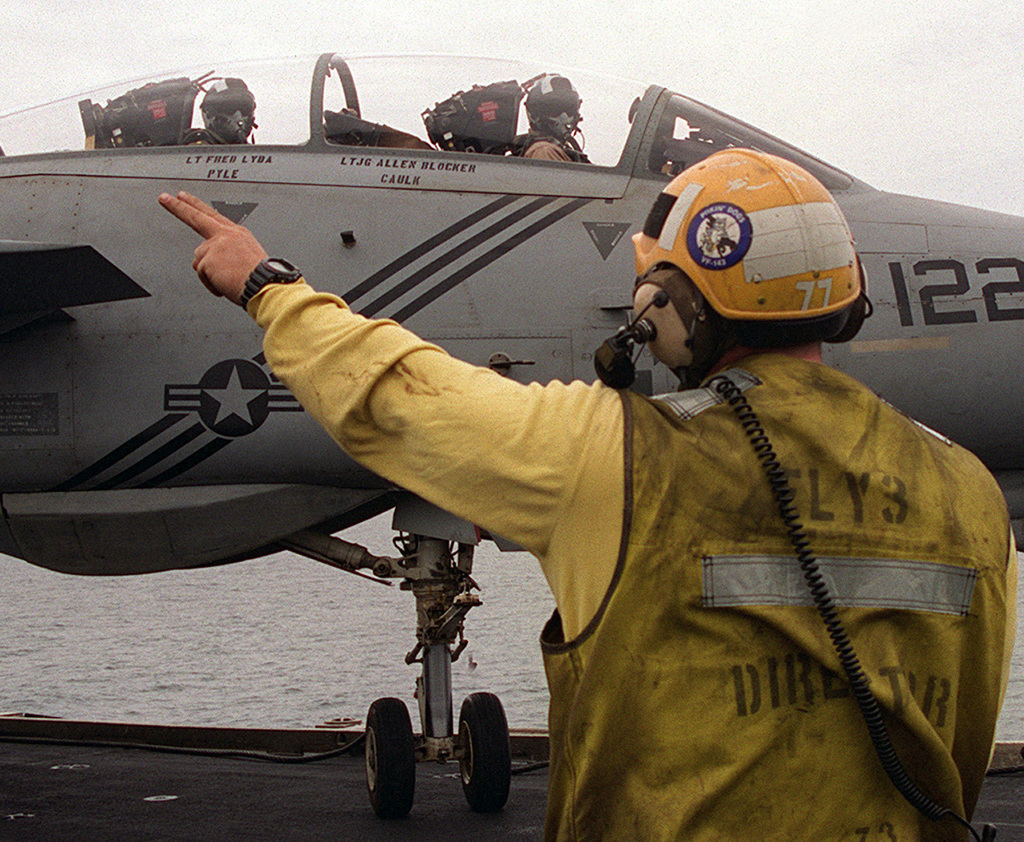 Onboard the Nimitz Class Aircraft Carrier, USS JOHN C. STENNIS (CVN-74), an Aircraft director for Fly 3 signals the pilot of a VF-143 F-14 Tomcat aircraft into position after daily flight operations. The Nuclear powered aircraft carrier is deployed to the Persian Gulf in support of the Southwest Asia build-up