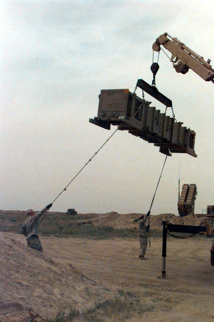 United States Army (USA) Private First Class (PFC) Michael Allard (left) and SPECIALIST Janathan Gainey hold on to guide ropes attached to a Patriot Missile tube at Ahmed Al Jaber Air Base, Kuwait, in support of Operation SOUTHERN WATCH 1998