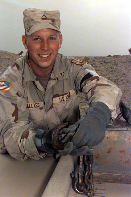 United States Army (USA) Private First Class (PFC) Michael Allard secures the chains of a hoist to a Guided Missile Transport of a Patriot Missile tube, at Ahmed Al Jaber Air Base, Kuwait, in support of Operation SOUTHERN WATCH 1998