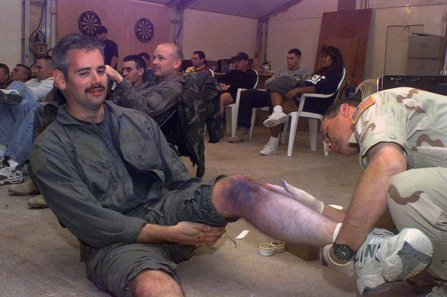 Lieutenant Colonel (LTC) Randy Dobbins, senior medical officer attached to the 16th Special Operations Wing (SOW), Hurlbert Field, Florida, simulates a crushed leg by applying a special makeup to United States Air Force (USAF) STAFF Sergeant (SSGT) Alan Cunningham, an Airborne Radio Operator with the 8th Special Operations Squadron (SOS), at Ali Al Salem Air Base, Kuwait, during Operation SOUTHERN WATCH 1998