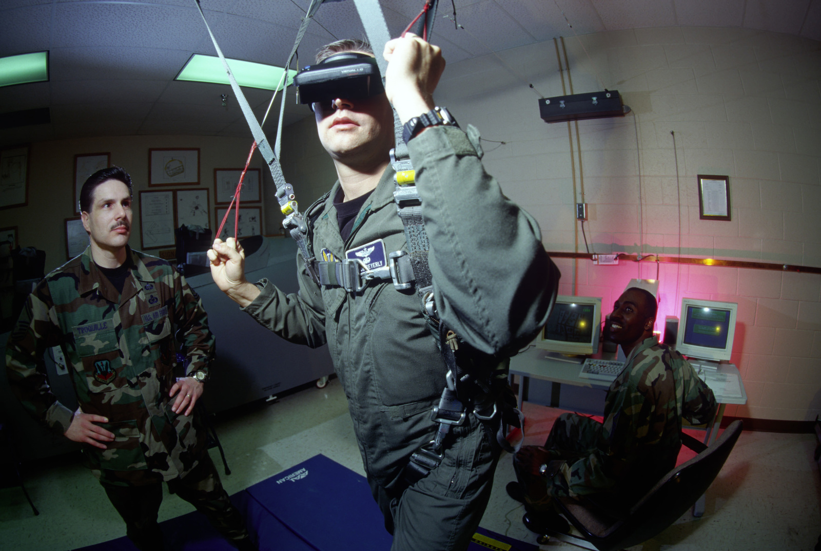 US Air Force (USAF) Captain (CPT) Bruce Beyerly, practices parachute landings using special 3-D goggles as USAF MASTER Sergeant (MSGT) Garrett Troquille, Life Support Superintendent, looks on inside the Life Support Center at Mountain Home Air Force Base, Idaho (ID). From AIRMAN Magazine April 1998 Issue