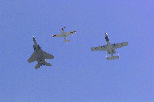 A US Air Force F-15 Strike Eagle (Left), A P-51 Mustang and A-10 Thunderbolt II (Right) fly overhead. The gates to Luke Air Force Base, Arizona, opened Saturday morning and crowds started trickling onto base an hour earlier than expected. People walked, pushed strollers and were shuttled in busses to the base. An estimated 150,000 people attended the one-day event, the first to take place here in three years. A total of 87 airplanes in different shapes and sizes were displayed at the base