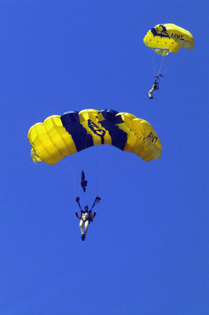 Members of the US Army's Golden Knights Parachute Team float towards the earth during Luke Day Airshow, in front of a crowd (Not shown) at Luke Air Force Base, Arizona. An estimated 150,000 people attended the one-day event, the first to take place here in three years