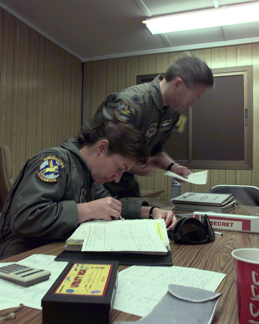 US Air Force (USAF) Technical Sergeant (TSGT) Tanzy Artrug, a USAF KC-10 Extender crewmember works on pre-mission paperwork as Lieutenant Colonel (LTCOL) Norm Thompson joins her at the table. Both are members of the 78th Air Refueling Squadron, Air Force Reserve (ARS-AFR), McGuire Air Force Base (AFB), New Jersey, deployed to the United Arab Emirates as part of the 4413th ARS (Provisional), in support of Operation SOUTHERN WATCH 1998