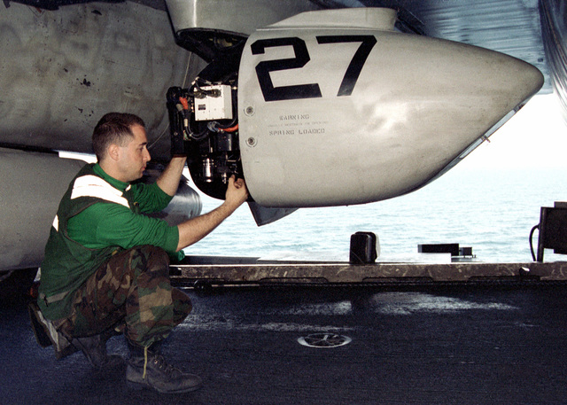 Photographer's Mate 3rd Class (PH3) Jason Stiles double checks the aperture and lens angle on an F-14 Tomcat mounted (TARPS) digital camera on board the conventional aircraft carrier USS INDEPENDENCE (CV 62). The INDEPENDENCE is forward deployed to the Persian Gulf in support of Operation SOUTHERN WATCH, 12 April 1998