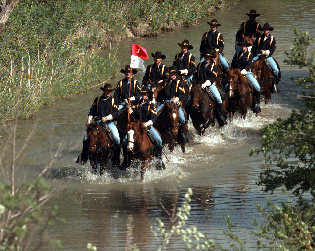 SSG Raymond Moss (right) and SGT Joseph Core (carrying unit flag) of the 1ST Cavalry Division, Horse Cavalry Detachment lead a ride through a creek as they prepare for an upcoming demonstration