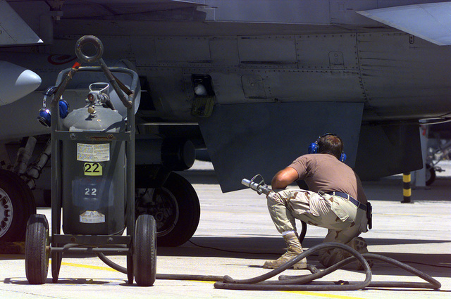 US Air Force (USAF) STAFF Sergeant (SSGT) Gary Klemme, a Crew CHIEF assigned to the185th Fighter Wing (FW), Iowa Air National Guard (ANG), Sioux City, Iowa, oversees an engine start on his F-16J Fighting Falcon fighter at Ahmed Al Jaber Airbase, Kuwait, in support of Operation SOUTHERN WATCH 1998
