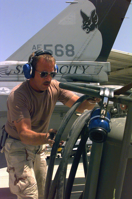 US Air Force (USAF) STAFF Sergeant (SSGT) Gary Klemme, a Crew CHIEF assigned to the185th Fighter Wing (FW), Iowa Air National Guard (ANG), Sioux City, Iowa, stores a fire hose after a successful F-16J Fighting Falcon engine start at Ahmed Al Jaber Airbase, Kuwait, in support of Operation SOUTHERN WATCH 1998