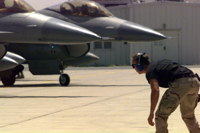 US Air Force (USAF) STAFF Sergeant (SSGT) Tyson Herbold, a crew chief assigned to the185th Fighter Wing (FW), Iowa Air National Guard (ANG), Sioux City, Iowa, looks over several launching F-16J Fighting Falcon fighters at Ahmed Al Jaber Airbase, Kuwait, in support of Operation SOUTHERN WATCH 1998