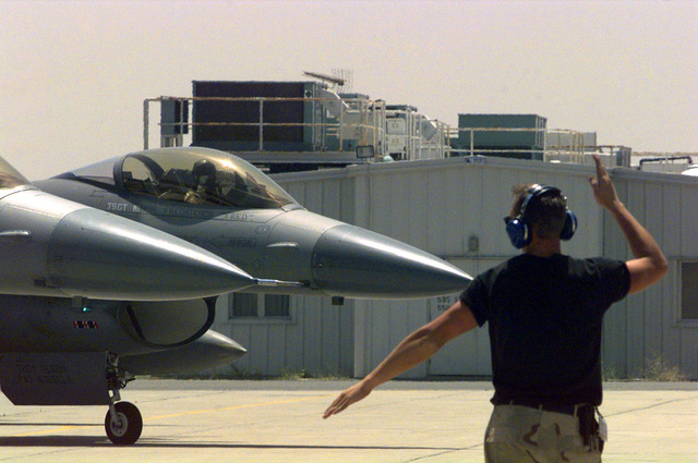 US Air Force (USAF) STAFF Sergeant (SSGT) Tyson Herbold, an F-16J Fighting Falcon crew chief with the185th Fighter Wing (FW), Iowa Air National Guard (ANG), Sioux City, Iowa, marshals his aircraft out on a mission, at Ahmed Al Jaber Airbase, Kuwait, in support of Operation SOUTHERN WATCH 1998