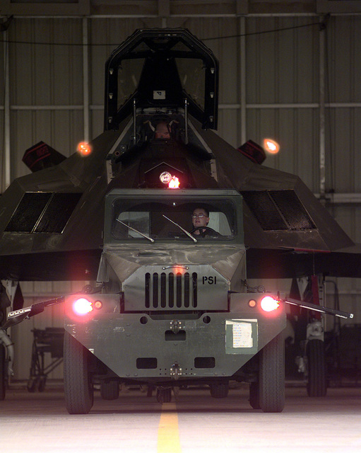 An aircraft tug pulls an F-117A Nighthawk stealth fighter assigned to the 9th Fighter Squadron (FS), 49th Fighter Wing (FW), Holloman Air Force Base (AFB), New Mexico, from its hanger at Ahmed Al Jaber Air Base, Kuwait, during Operation SOUTHERN WATCH 1998