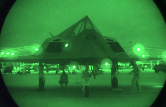 U S Air Force (USAF) maintenance personnel work under an F-117A Nighthawk stealth fighter assigned to the 9th Fighter Squadron (FS), 49th Fighter Wing (FW), Holloman Air Force Base (AFB), New Mexico, at Ahmed Al Jaber Air Base, Kuwait, in support of Operation SOUTHERN WATCH 1998. Night scope used