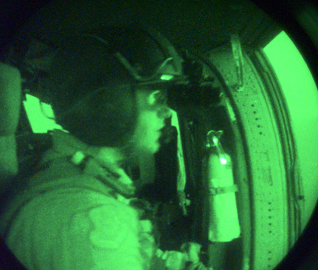 US Air Force (USAF) STAFF Sergeant (SSGT) Rob Ellenberg, a HH-60G Pave Hawk Flight Engineer with the 4412th Rescue Squadron (RS)(Provisional) wears night vision goggles while flying aboard an USAF MH-60G Pave Hawk helicopter, in support of Operation SOUTHERN WATCH 1998. Night scope used