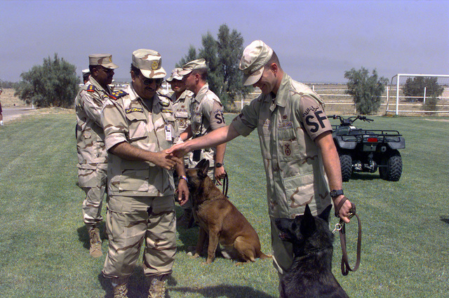 Kuwaiti Major General (MGEN) Nasser Al Juhail, Commander, Al Jaber Air Base, meets U S Air Force (USAF) Security Forces military working dog handler, AIRMAN First Class (A1C) Christopher Guild and his dog Arco, members of the 4406th Operations Group (OG), as they demonstrate their abilities before a group of senior Kuwaiti military officials, at Al Jaber Air Base, Kuwait, in support of Operation SOUTHERN WATCH 1998
