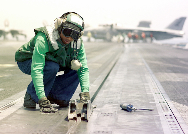 US Navy Aviation Boatswain's Mate 3rd Class (AB3) Peter Duncan cleans the shuttle of catapult number four in between flight operations aboard the nuclear powered aircraft carrier USS JOHN C. STENNIS (CVN 74). The JOHN C. STENNIS is currently on a scheduled six month deployment to the Persian Gulf. Operation SOUTHERN WATCH, 4 May 1998