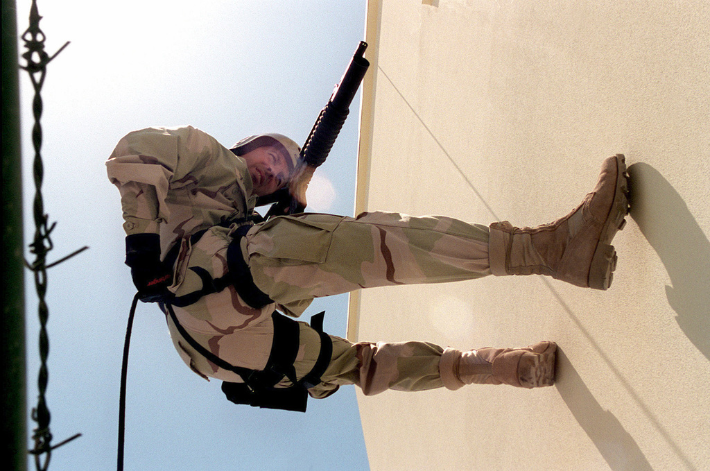 US Navy Boatswain's Mate 1ST Class (BM1) Thomas L. Spoerer rappels down the wall of a building at the Administrative Support Unit, Bahrain, during a training drill. Operation SOUTHERN WATCH, 11 May 1998